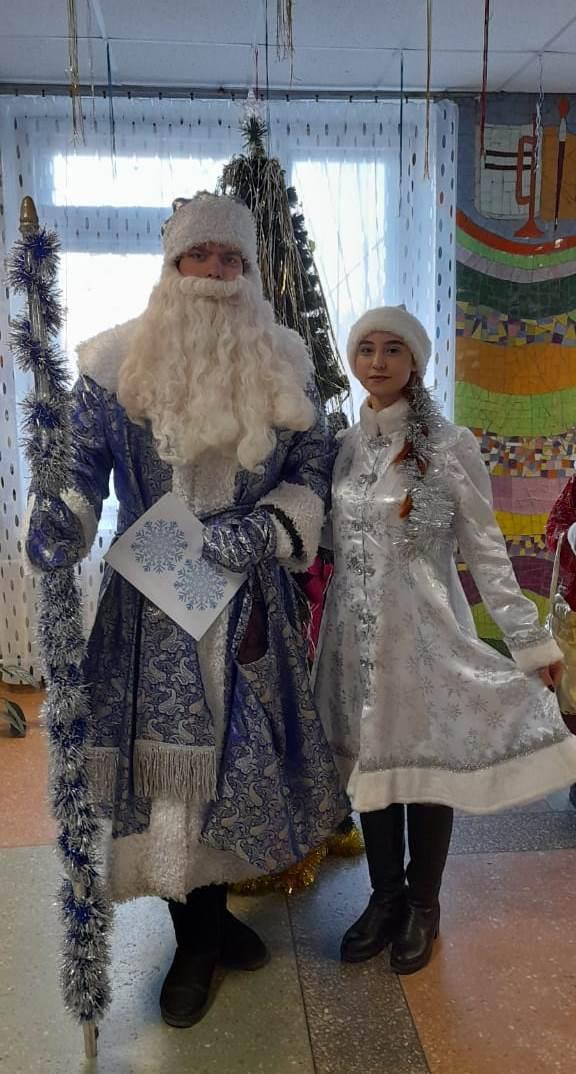 Дед Мороз и Снегурочка вручают подарки